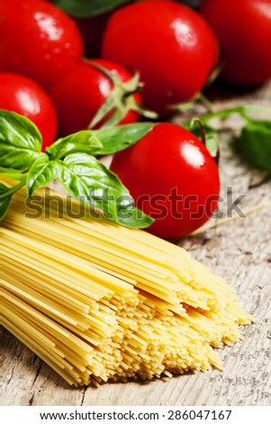 Dry Italian pasta Capellini with tomato and basil on old wooden table, selective focus - stock photo