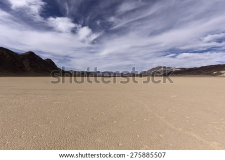 Dry lake bed in Mojave desert with cracked mud on a lake floor, blue sky, clouds and mountains. Racetrack Playa. Death Valley national park. California. USA. - stock photo