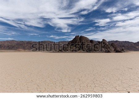 Dry lake bed with cracked mud on a lake floor, blue sky, clouds and mountains. Racetrack Playa. Death Valley national park. California. USA. - stock photo