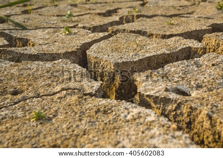 Dry land texture. Cracked dry clay soil as background. Selective focus. - stock photo