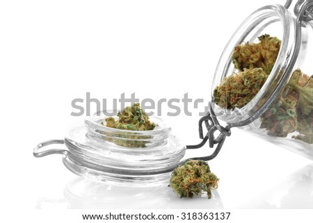 Dry medical cannabis in jar isolated on white - stock photo