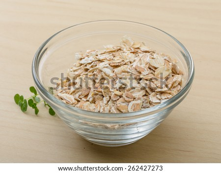 Dry oats pile in the glass bowl - stock photo