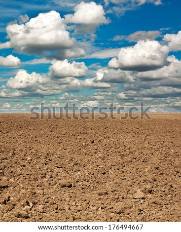 Dry plowed earth agricultural land, on background blue sky and white clouds - stock photo