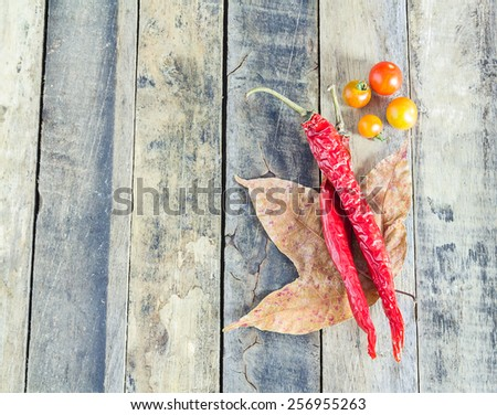 Dry red hot chili peppers and tomato on wooden background - stock photo