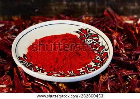 Dry red paprika on a plate with paprika background - stock photo