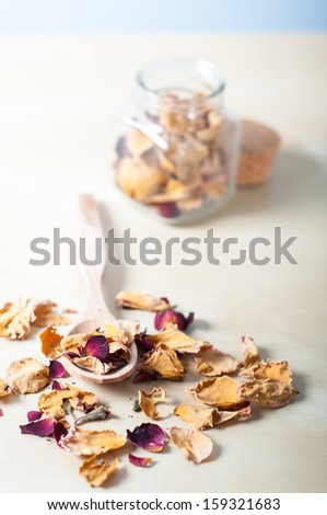 Dry rose petals with a wooden spoon and a small glass pot - stock photo