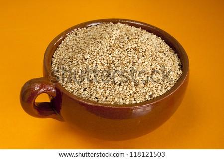 Dry sesame in ceramic bowl on orange background - stock photo