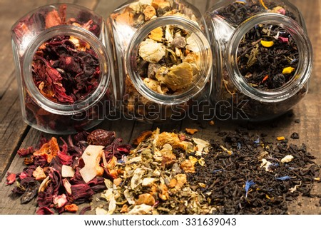 Dry tea in glass jars on wooden rustic background. Leaves of red, green and black tea. Macro photo. Rustic style and concept. Healthy drink in cold period.  - stock photo