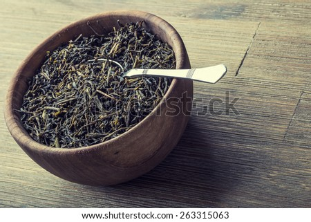 Dry tea in wooden plate on wooden table. Antique spoon as scoop dried tea  - stock photo