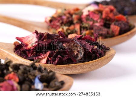Dry tea in wooden plates and spoons, on white background. Leaves of red, green and black tea. Macro photo. - stock photo