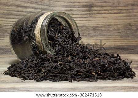 Dry tea leaves for black tea and glass jar on wooden background - stock photo