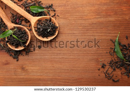 Dry tea with green leaves in wooden spoons, on wooden background - stock photo