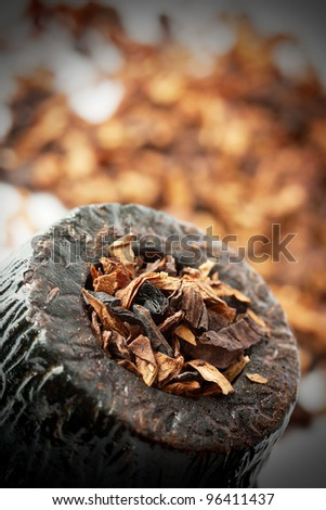 Dry tobacco and pipe with vignette - stock photo