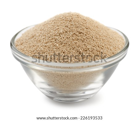 Dry yeast granules in glass bowl isolated on white - stock photo