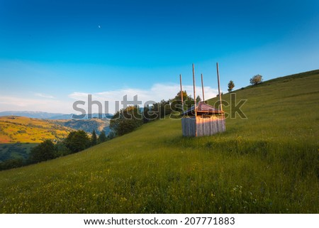 Dryer hay in summer mountain landscape with flowering grassland.  - stock photo