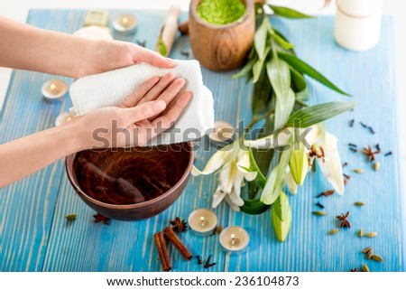 Drying hands with bath towel on wooden table with spa stuff on background - stock photo