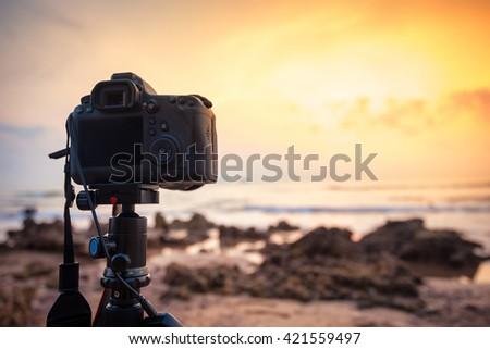 DSLR Camera capturing sunrise of beach view. - stock photo