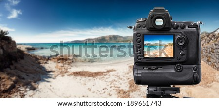 DSLR Camera on tripod shooting in the beach - stock photo