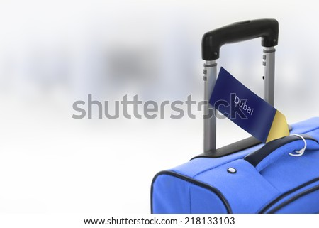 Dubai. Blue suitcase with label at airport. - stock photo