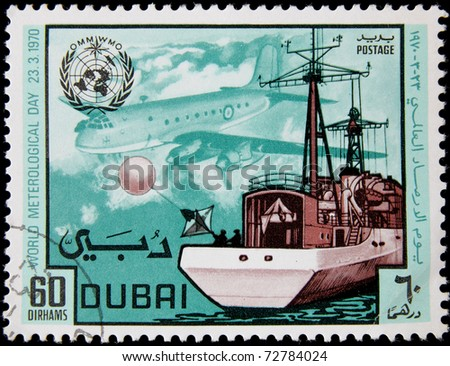 DUBAI - CIRCA 1970 : A post stamp printed in Dubai show ship and plane, devoted world meteorological day, circa 1970 - stock photo