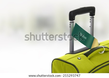 Dubai. Green suitcase with label at airport. - stock photo