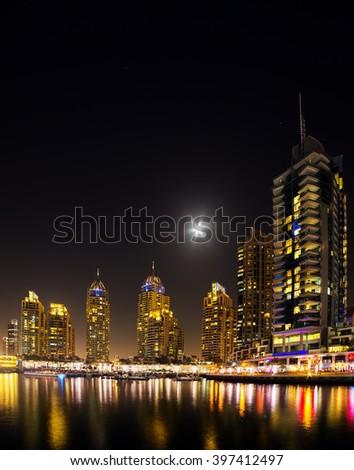 Dubai marina illuminated in night, United Arab Emirates - panorama of skyscrapers - stock photo