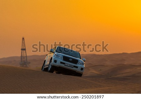 DUBAI - OCTOBER 21: Driving on jeeps on the desert, traditional entertainment for tourists on October 21, 2014 in Dubai - stock photo