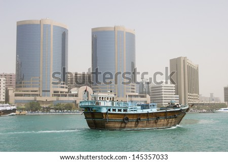 Dubai UAE A dhow old wooden sailing vessel cruises down Dubai Creek  - stock photo
