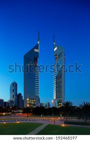 DUBAI, UAE - APR 12: A profile of the iconic Emirates Towers in Dubai, UAE at dusk as viewed from DIFC on Apr 12, 2014 in Dubai, UAE. DIFC is the financial hub of Dubai. - stock photo