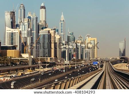 DUBAI, UAE - DECEMBER 15, 2015:  Modern architecture of Dubai Marina, UAE, seen from a metro car. Traveling in Dubai, UAE. - stock photo