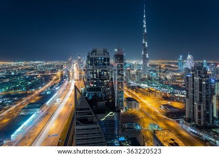DUBAI, UAE - DECEMBER 17, 2015: Scenic aerial view of Dubai's modern architecture at night with Sheikh Zeyed road and Burj Khalifa, the tallest building in the world. - stock photo