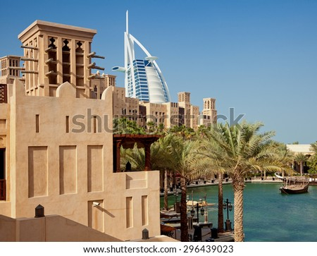 DUBAI, UAE - JANUARY 14, 2013: Traditional windcatcher and Arabic style buildings of Madinat Jumeirah in front of Burj Al Arab. Burj Al Arab is a luxury 7 star hotel, built on an artificial island. - stock photo