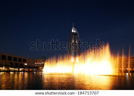 DUBAI, UAE - MAR 24: The Dancing Fountain of Dubai performs to the beat of the selected music at dusk on Mar 24, 2014 in Dubai, UAE. The fountain is overlooked by Dubai Mall and the Address Hotels - stock photo
