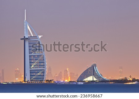 DUBAI, UAE - MARCH 7: View of the luxury hotel Burj Al Arab and Jumeirah Beach Hotel at sunset, on March 7, 2013  in Dubai, United Arab Emirates.  - stock photo