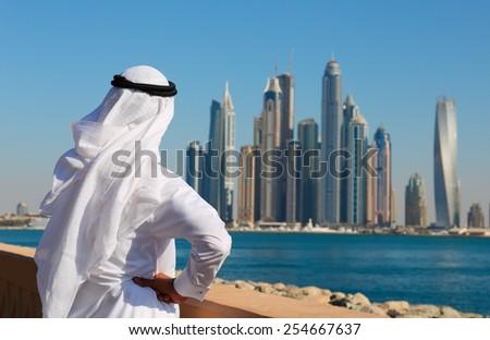 DUBAI, UAE - NOVEMBER 7, 2013: Modern buildings in Dubai Marina. Man in Arab dress looks at the city - stock photo