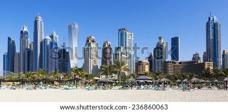 DUBAI, UAE - NOVEMBER 28: Panoramic view of modern buildings with beach in Dubai Marina, Dubai, UAE. Taken on 28 November 2014 in Dubai.  - stock photo
