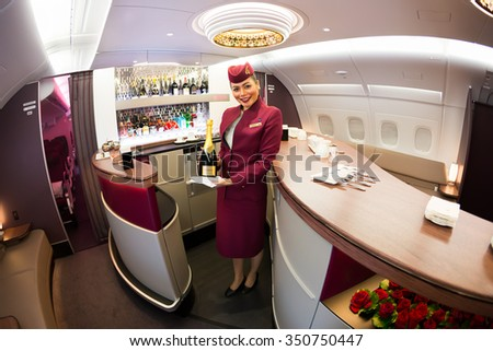 Dubai, UAE - NOVEMBER 10, 2015: Qatar Airways Airbus A380 cabin crew member, Qatar Airways flight attendant, Qatar Airways stewardess, Airbus A380 upper deck lounge on November 10, 2015 in Dubai - stock photo