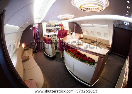 Dubai, UAE - NOVEMBER 10, 2015: Qatar Airways Airbus A380 cabin crew member, Qatar Airways flight attendant, Qatar Airways stewardess, Airbus A380 upper deck bar, lounge on November 10, 2015 in Dubai - stock photo