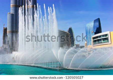 DUBAI, UAE - NOVEMBER 14: The Dancing fountains downtown and in a man-made lake in Dubai, UAE on November 14, 2012. The Dubai Dancing fountains are world's largest fountains with height 150 m. - stock photo