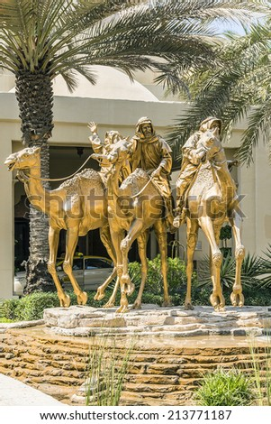 DUBAI, UAE - SEPTEMBER 30, 2012: Huge gold camels sculptures by Danie de Jager decorated entrance in 5 star hotel One&Only Royal Mirage (451 rooms, 65 acres of lush green lawns, 1 km beachfront). - stock photo
