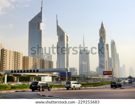 DUBAI, UAE - SEPTEMBER 8: The Dubai cityscape and Emirates towers on September 8, 2013 in Dubai, UAE. In the city of artificial channel length of 3 kilometers along the Persian Gulf. - stock photo