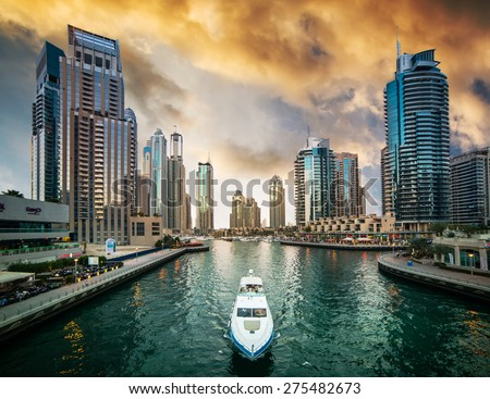 Dubai, United Arab Emirates - December 14, 2013: Modern skyscrapers and water channel with boats of Dubai Marina at sunset, United Arab Emirates - stock photo