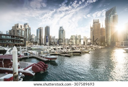 Dubai, United Arab Emirates - December 14, 2013: Panoramic view with modern skyscrapers and water pier of Dubai Marina at sunset, United Arab Emirates - stock photo