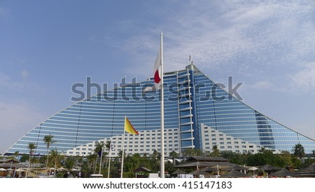 Dubai, United Arab Emirates - February 12, 2016 : Jumeirah Beach hotel surrounded by green palm trees on a sunny day. Voted the Best Hotel in the Middle East for two years in a row. - stock photo