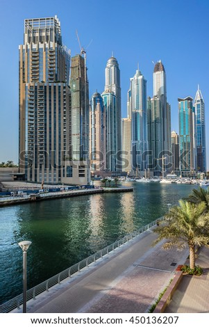 DUBAI, UNITED ARAB EMIRATES - SEPTEMBER 8, 2015: Modern skyscrapers and embankment in famous Dubai Marina. Marina - artificial canal city, carved along a 3 km stretch of Persian Gulf shoreline. - stock photo