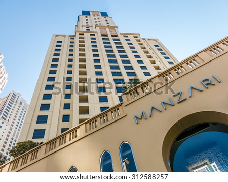 DUBAI, UNITED ARAB EMIRATES (UAE) - JAN 25, 2014: Highrise apartment building and facade of Manzari store at The Walk Promenade in the Marina district - stock photo