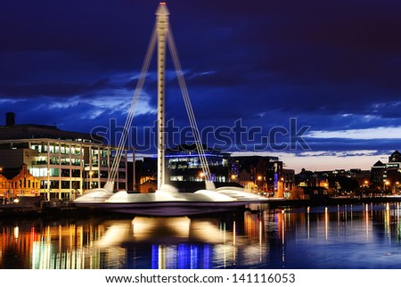 DUBLIN, IRELAND - AUGUST 23: Samuel Beckett Bridge, a cable-stayed bridge by architect Santiago Calatrava, opening for maintenance at night time, on August 23, 2011 in Dublin, Ireland - stock photo