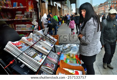 DUBLIN, IRELAND - FEBRUARY 19: A woman reads newspaper headlines at a newsstand along O'Connell Street on February 19, 2015 in Dublin, Ireland.  - stock photo