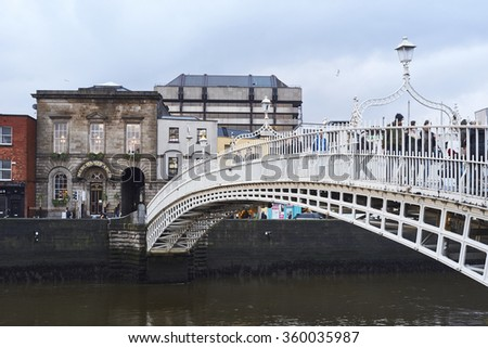 DUBLIN, IRELAND - JANUARY 05: Perspective view of Ha'penny Bridge over Liffey river. The bridge is the main access point to the touristic area of Temple Bar. January 05, 2016 in Dublin - stock photo