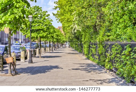 DUBLIN, IRELAND - MAY 25: a tree lined pavement next to St. Stephen's Green on May 25, 2013 in Dublin, Ireland. Dublin is a popular tourist destination with 6.5 million visitors from overseas in 2012. - stock photo